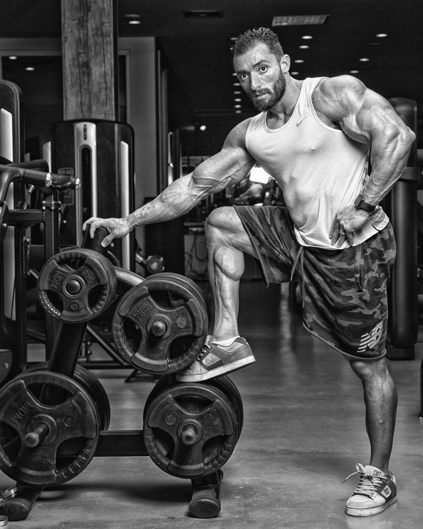 Abtin Shekarabi leaning against weight plates during a photo shoot