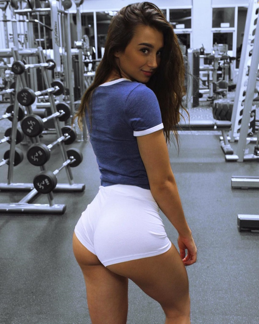 Amber Gianna posing in white shorts in a gym displaying her awesome glutes