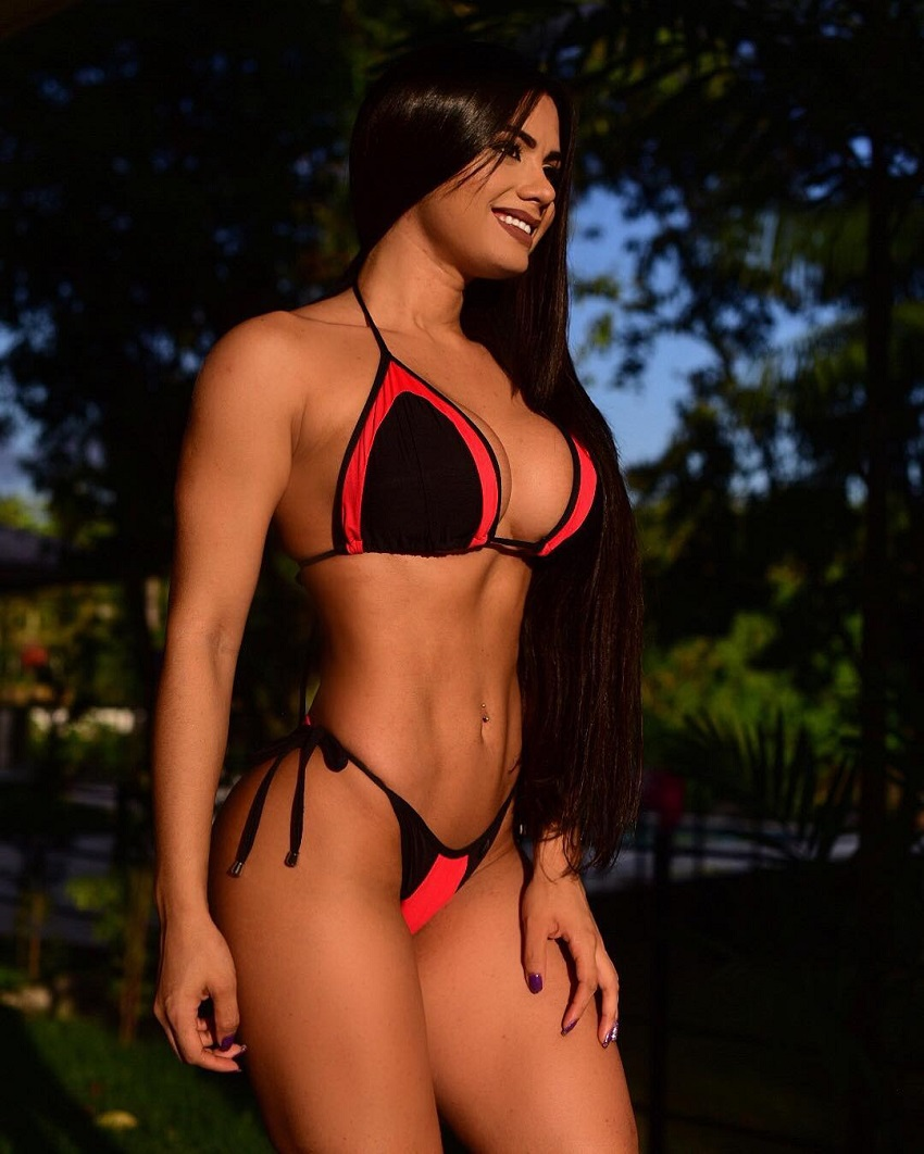 Bruna Barreto standing in the woods in her bikini looking lean
