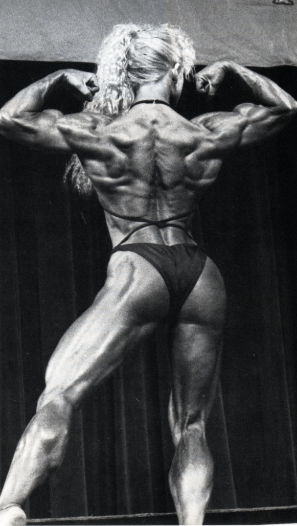 Ellen van Maris doing a back double biceps flex on the bodybuilding stage