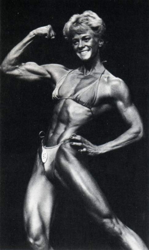 Ellen van Maris during her early bodybuilding days flexing her biceps on the stage