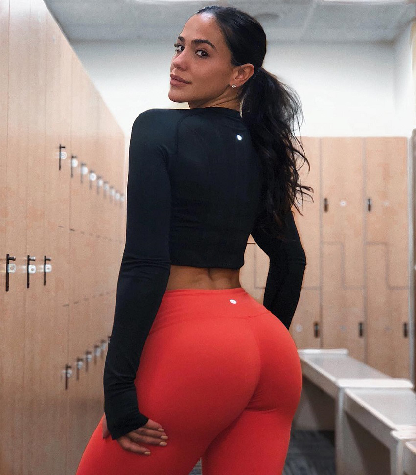 Giuliana Ava standing in a gym locker room displaying her curvy glutes in red leggings