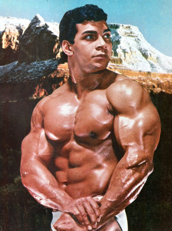 Harold Poole flexing shirtless with a mountain in the background