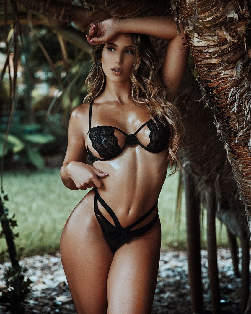 Isabella Buscemi posing by a tree in her black lingerie looking fit and lean