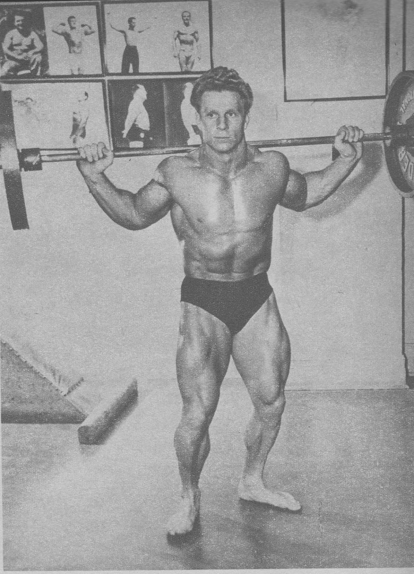 Jack Delinger standing shirtless with a heavy barbell on his back