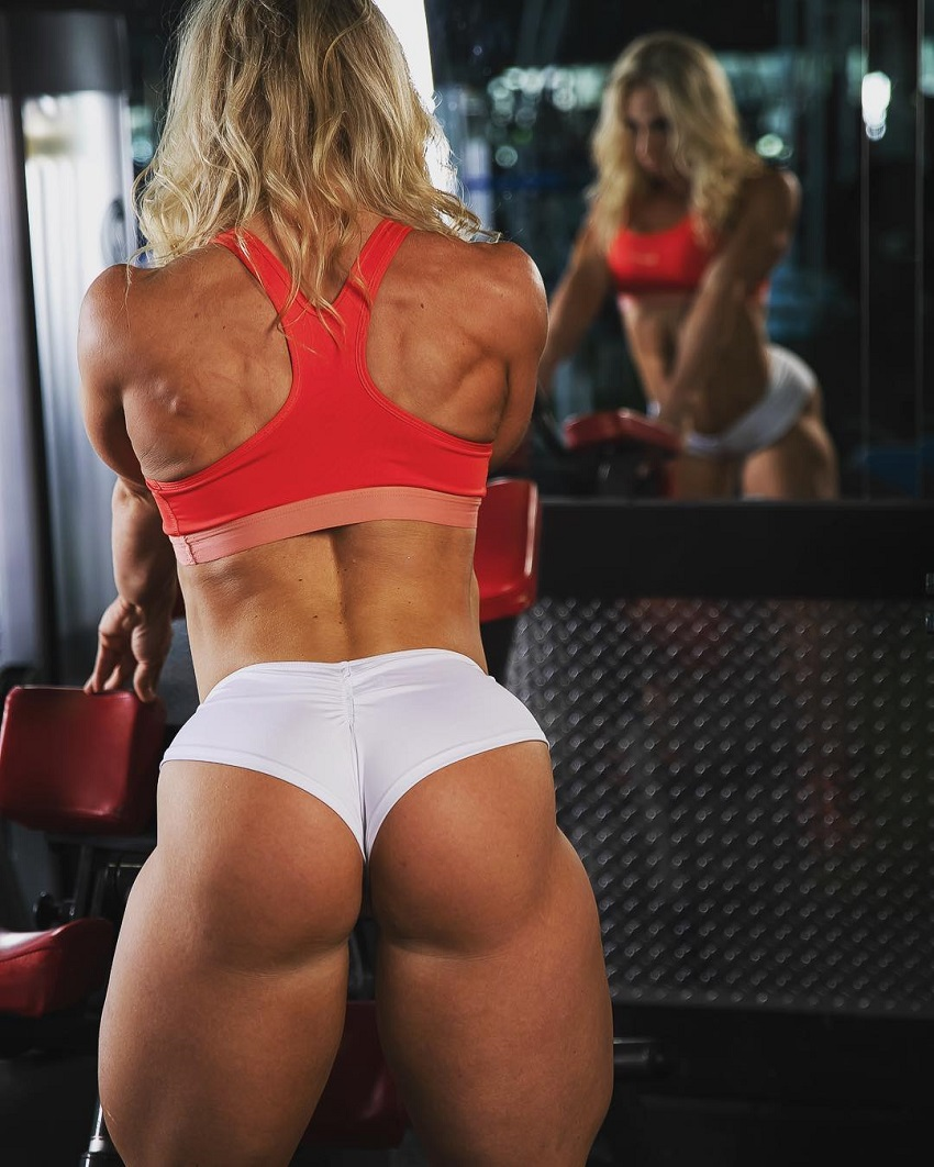 Jazmin Gillespie standing in front of a mirror in a gym, looking strong and fit