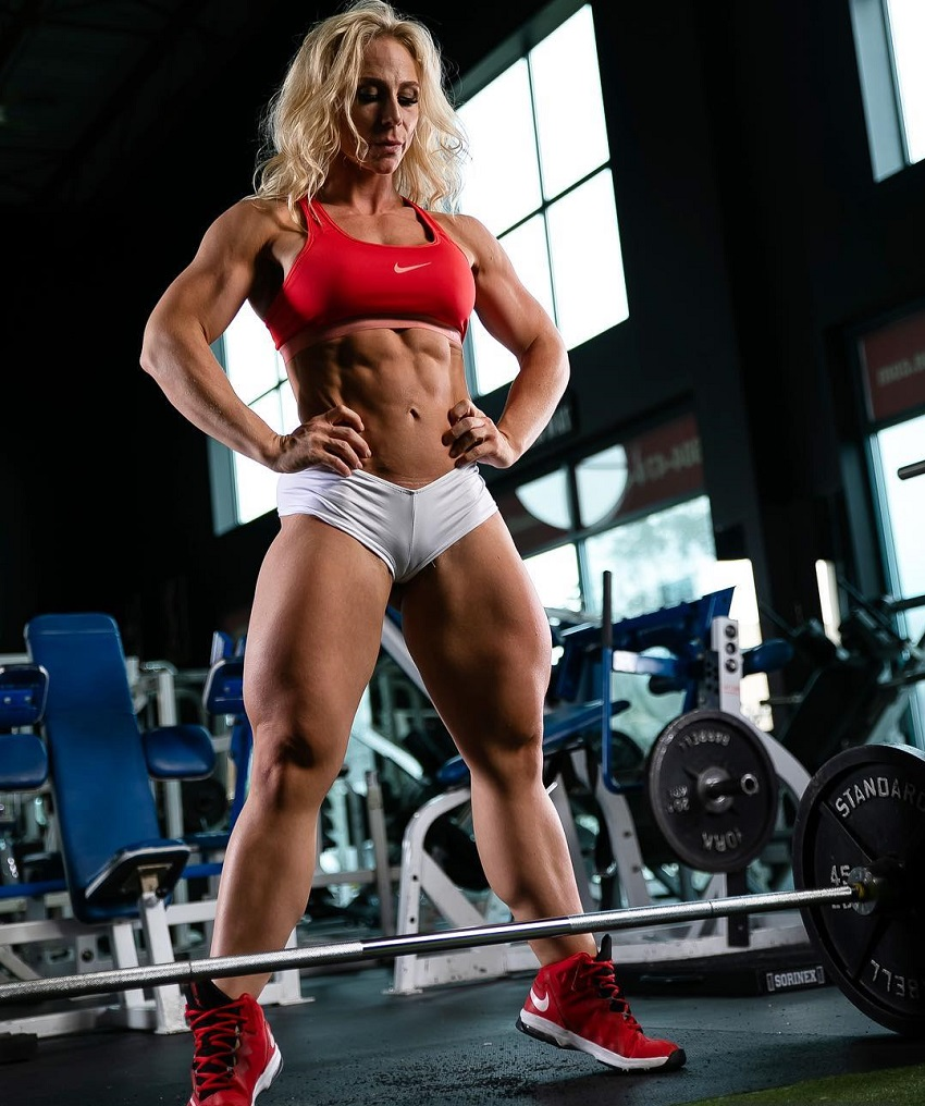Jazmin Gillespie standing in front of a barbell loaded with weights looking strong and ripped