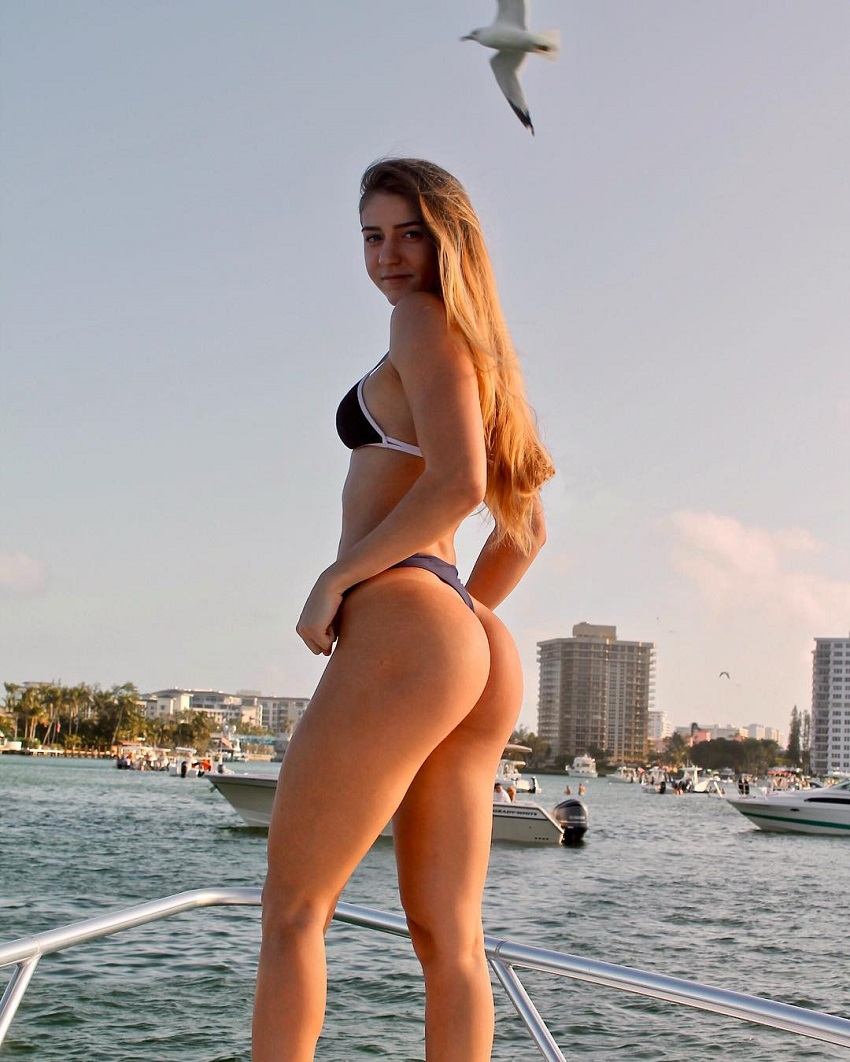 Julia Taylor standing on a boat in the sea near a city showing off her curvy legs and glutes