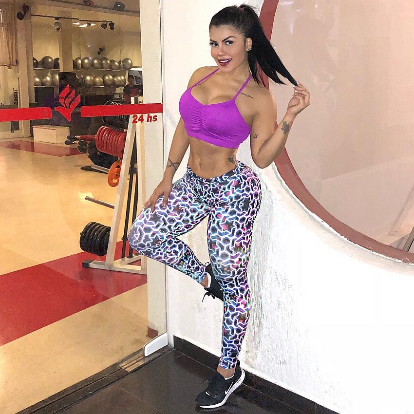 Karol Prado leaning against a wall in the gym with weights and fitness instructors, looking curvy and fit