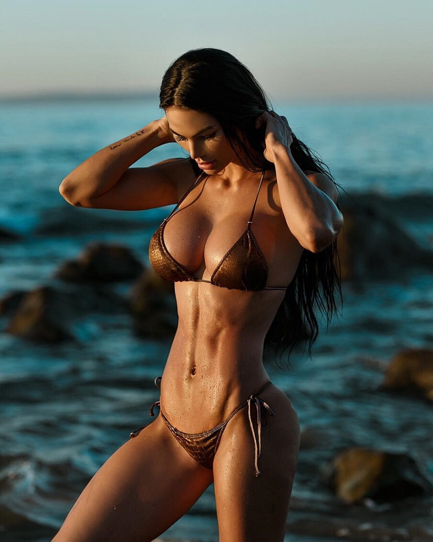 Katelyn Runck standing on a rock by the sea looking fit and ripped