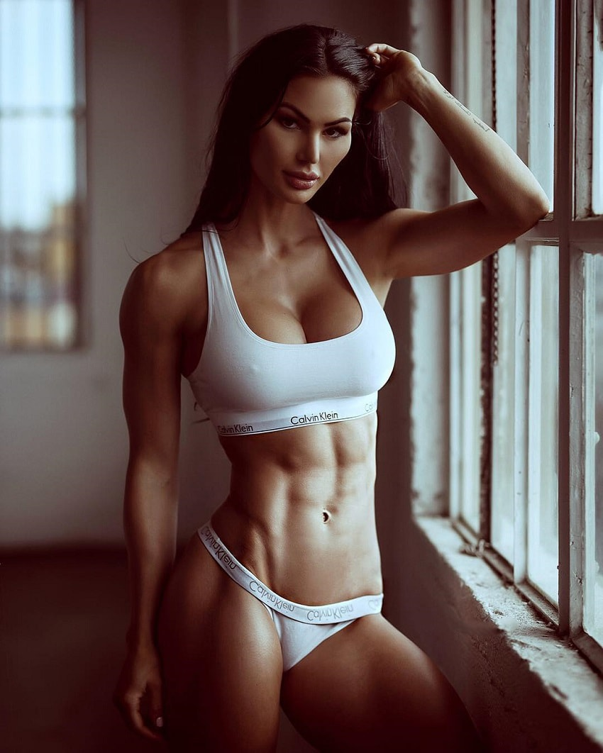 Katelyn Runck standing by a window posing in white lingerie looking ripped and toned