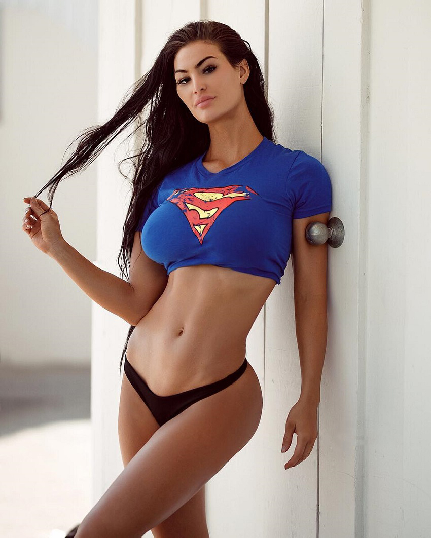 Katelyn Runck posing for a photo in a superman outfit looking fit and toned