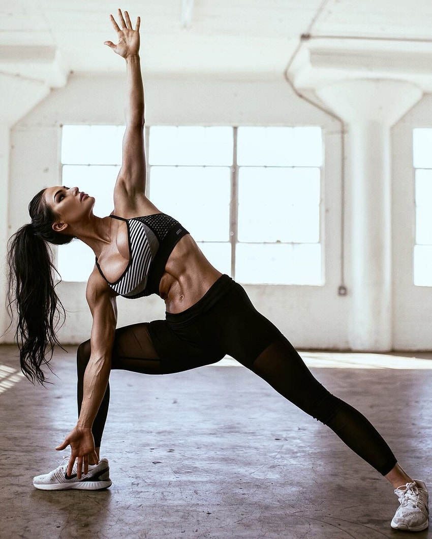 Katelyn Runck stretching in a big and empty room looking ripped