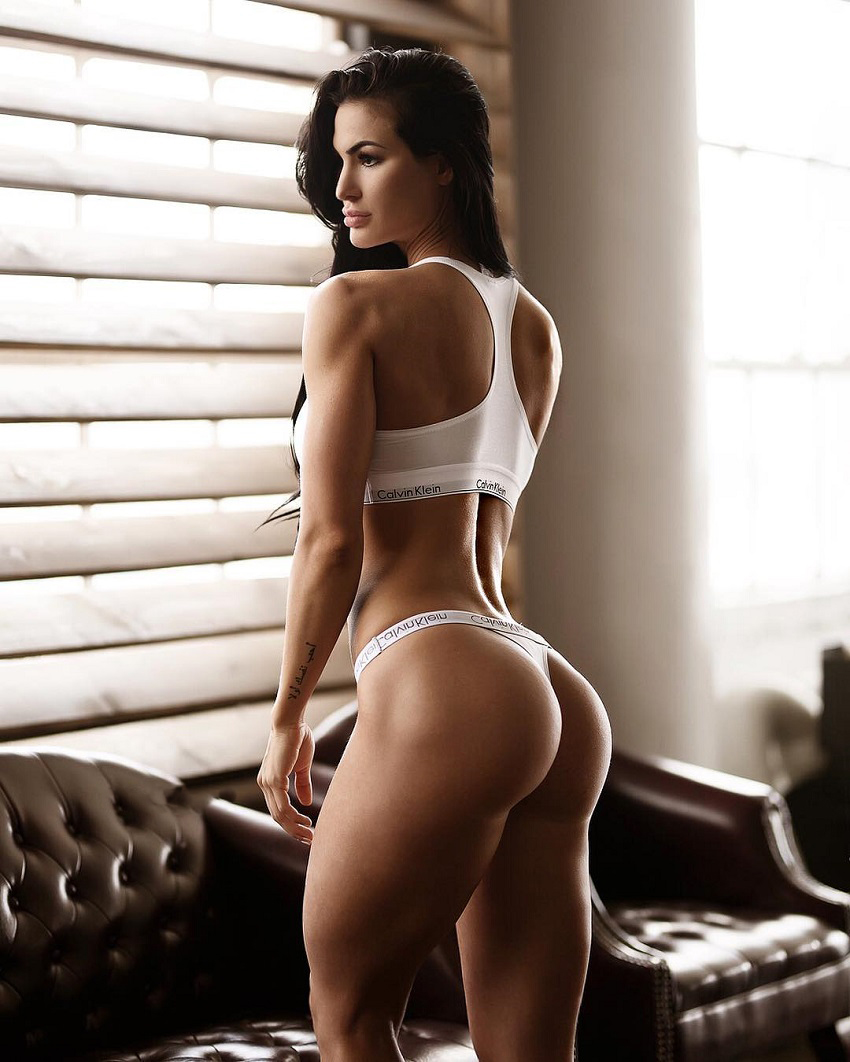Katelyn Runck standing by a dumbbell rack looking fit and curvy