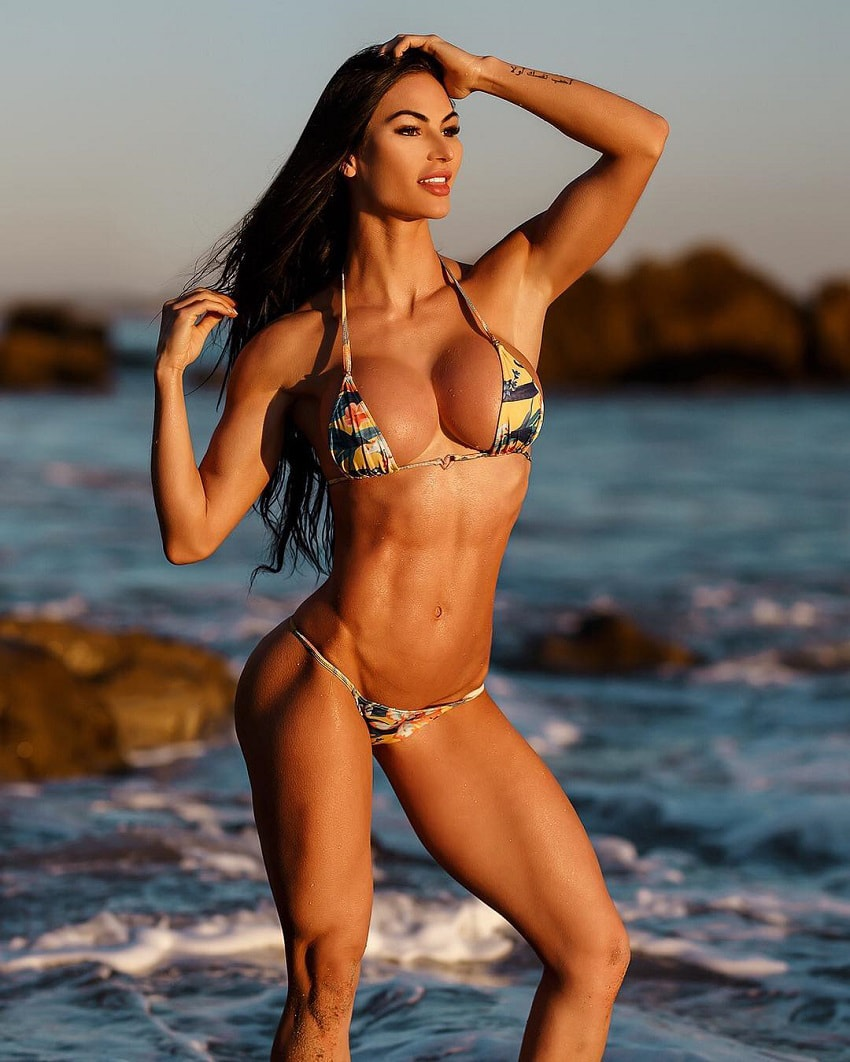 Katelyn Runck posing in a bikini on the beach looking fit and toned