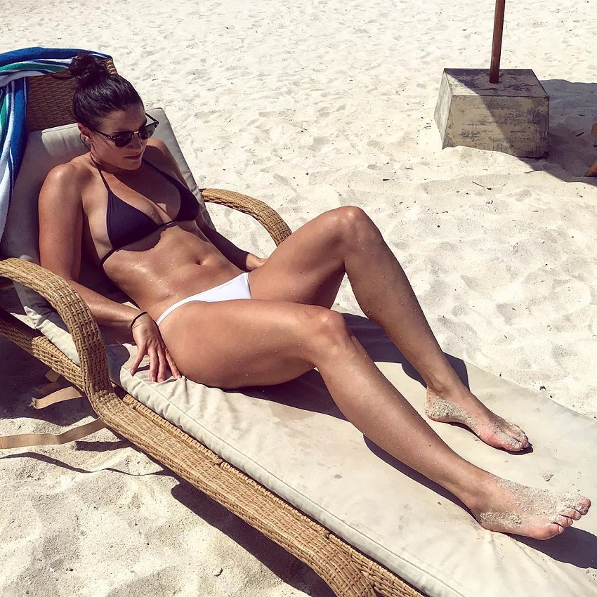 Michelle Jenneke lying on a sand beach looking fit