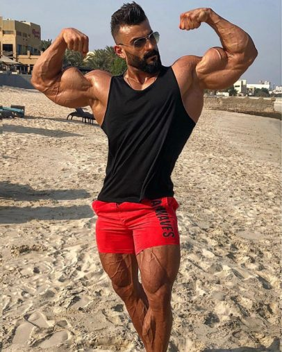 Mohamed El Qadi doing a front double biceps flex looking huge and ripped