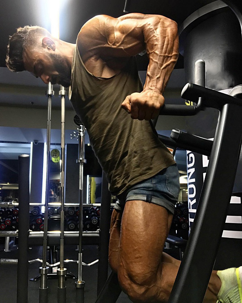 Mohamed El Qadi doing dips in a gym looking ripped and swole