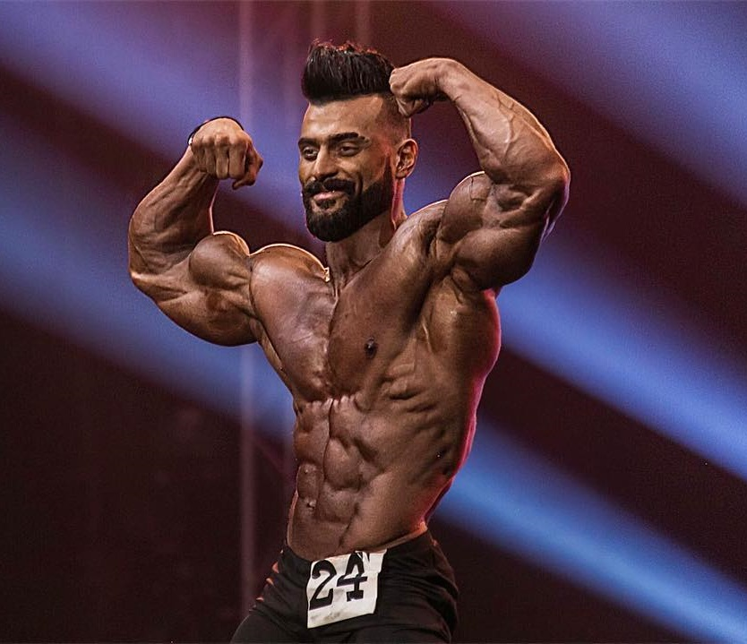 Mohamed El Qadi flexing on a bodybuilding stage