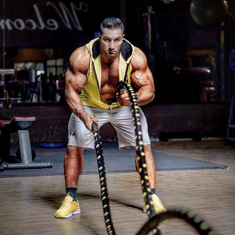 Rouhollah Mirhoseini performing a battle ropes exercise looking ripped and swole