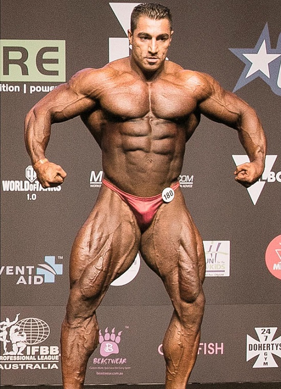 Rouhollah Mirhoseini standing on the bodybuilding stage looking riped