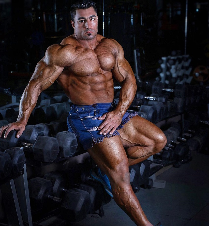 Rouhollah Mirhoseini sitting on a rack of dumbbells looking huge and swole