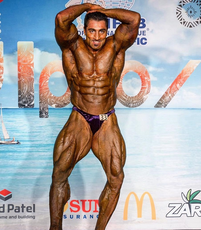 Rouhollah Mirhoseini showcasing his bulging abs in a bodybuilding contest