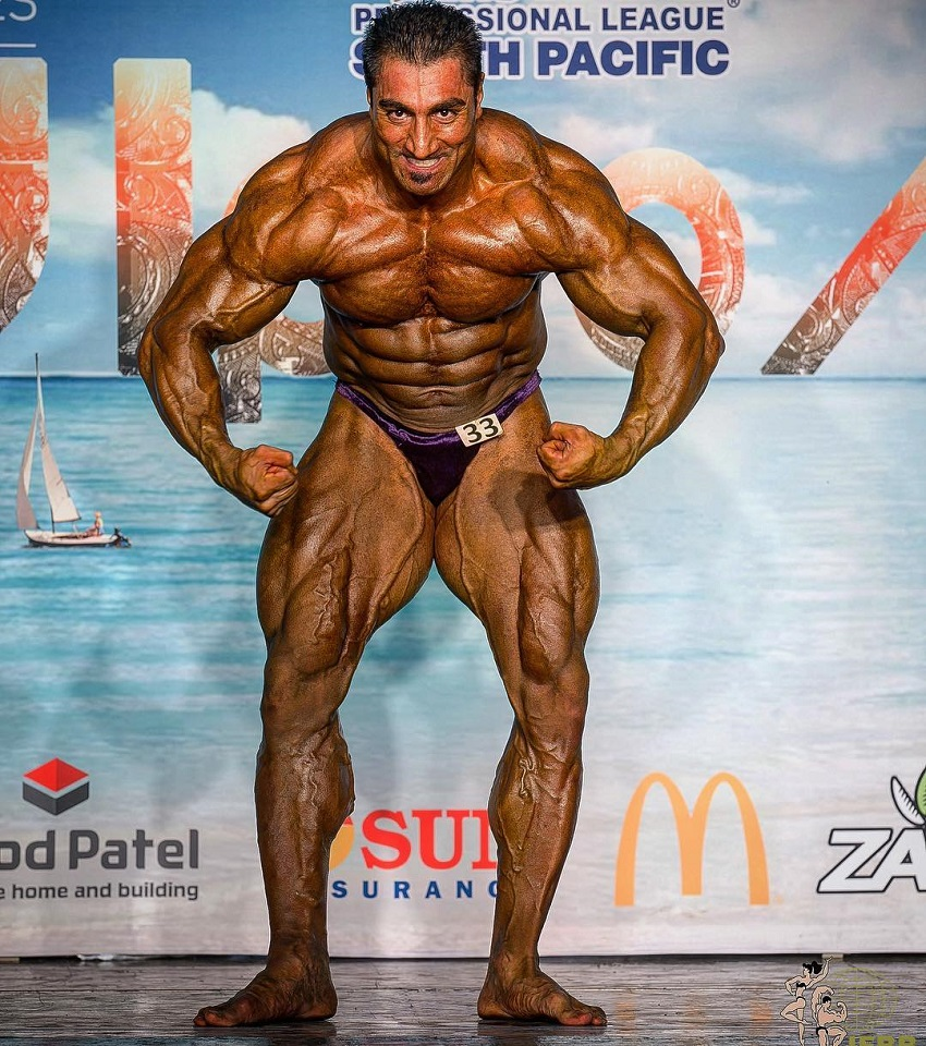 Rouhollah Mirhoseini posing on a bodybuilding stage looking huge and ripped