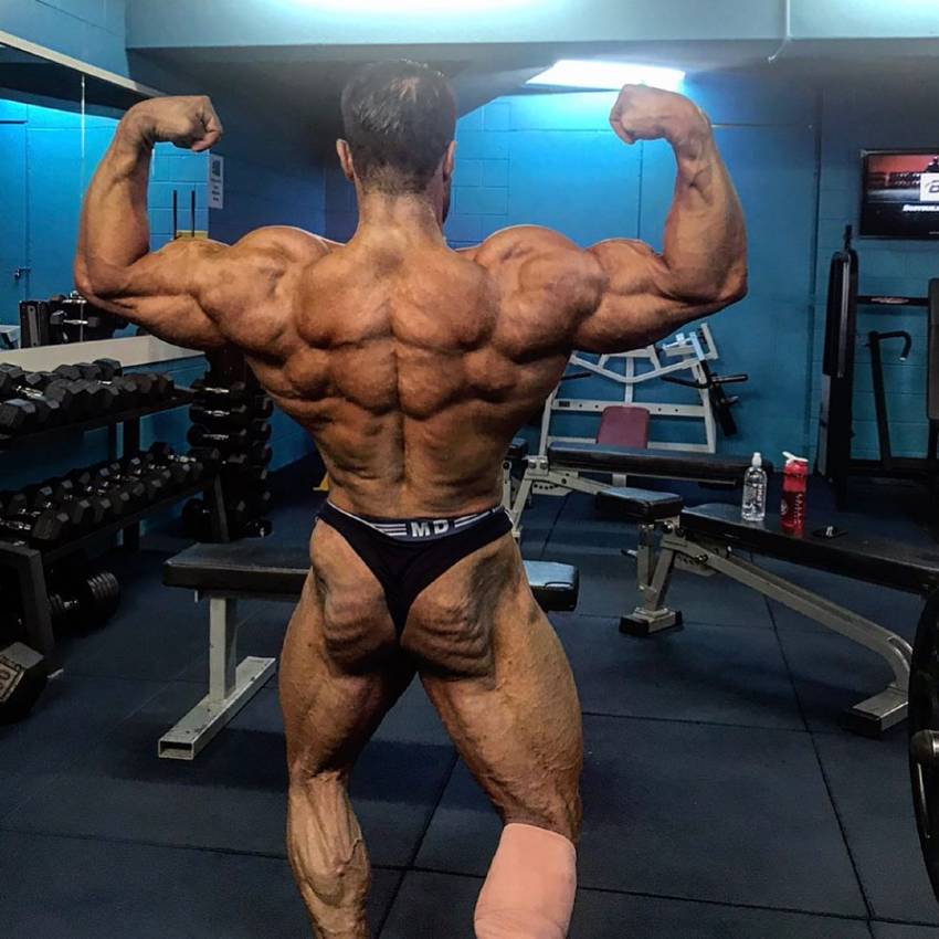 Rouollah Mirhoseini hitting a shirtless back double biceps pose