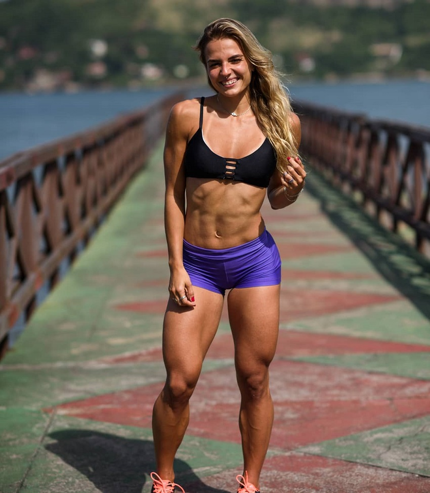 Vanessa Garcia standing on a bridge displaying her toned figure for a photo