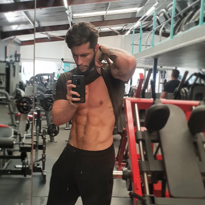 Vince Azzopardi flexing his abs in a gym selfie