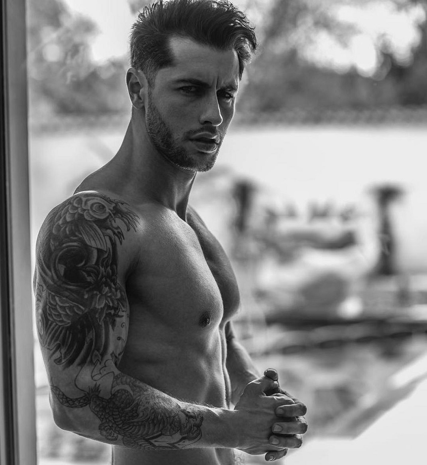 Vince Azzopardi standing shirtless on a balcony looking strong and fit