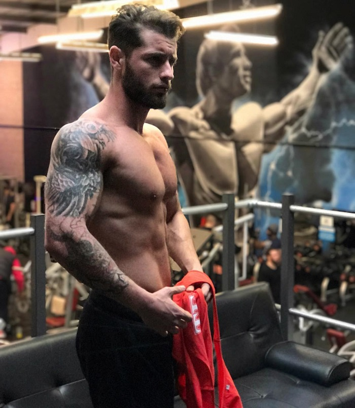 Vince Azzopardi posing shirtless in a gym with a picture of Arnold Schwarzenegger in the background