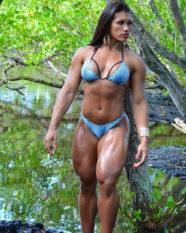 Alessandra Alvez Lima posing outdoors in a jungle, looking fit and lean in her green bikini