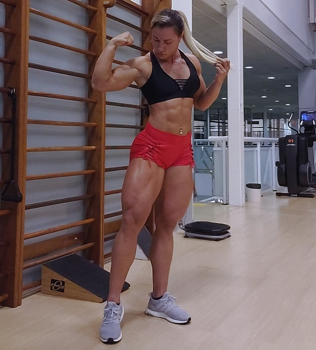 Carla Inhaia flexing her biceps and quads looking strong