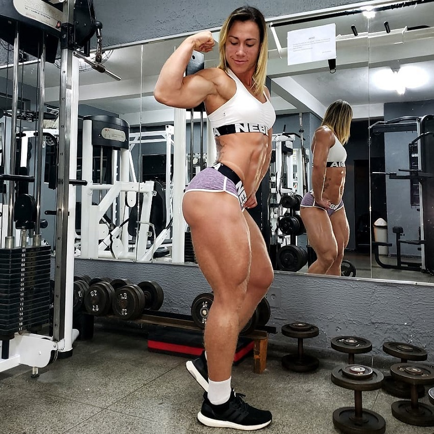 Carla Inhaia flexing her biceps in a gym