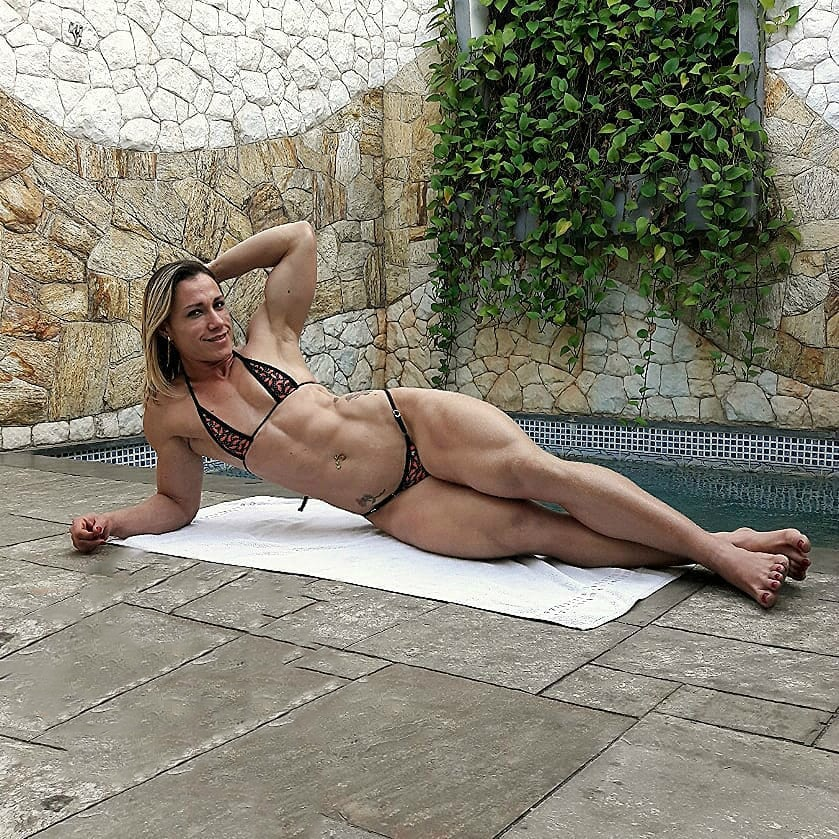 Carla Inhaia lying on a white blanket wearing a bikini, looking fit and curvy