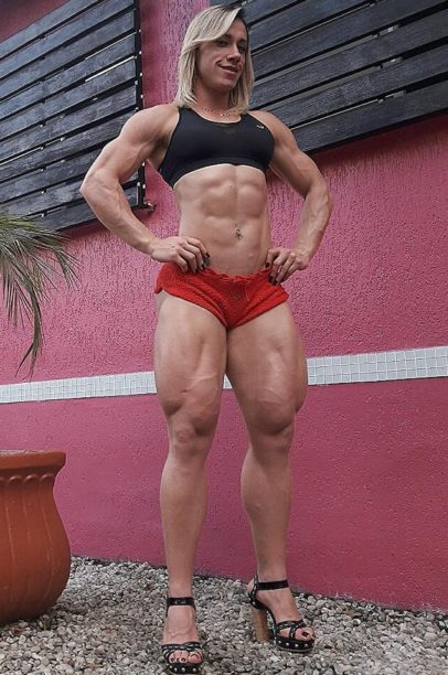 Carla Inhaia showcasing her ripped abs and legs for the photo