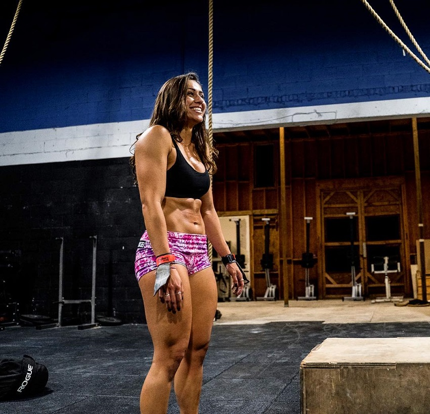 Cristina Bayardelle standing in a CrossFit gym, looking at someone and smiling