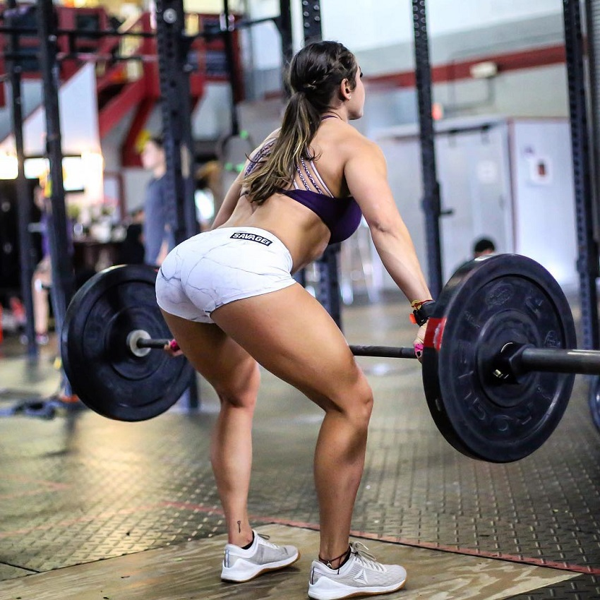 Cristina Bayardelle lifting a heavy barbell looking curvy and fit