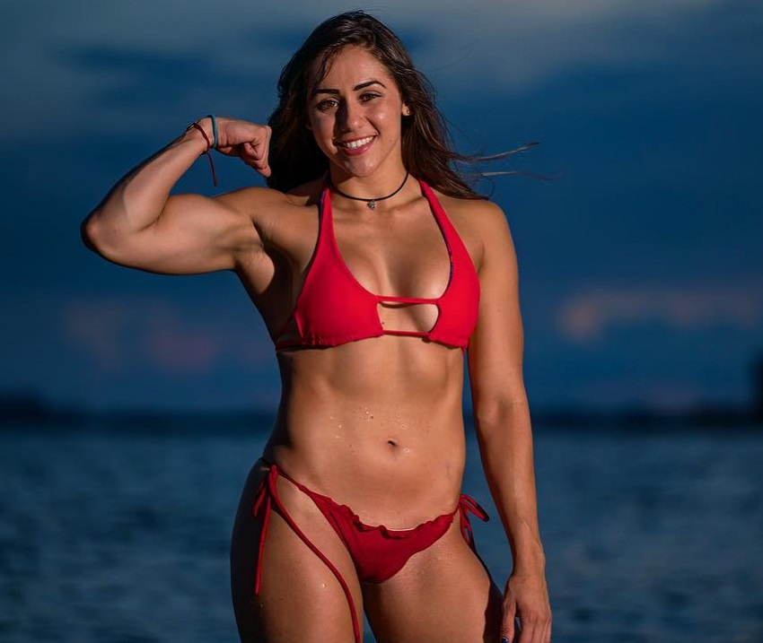 Cristina Bayardelle flexing her biceps in a red bikini looking toned and fit