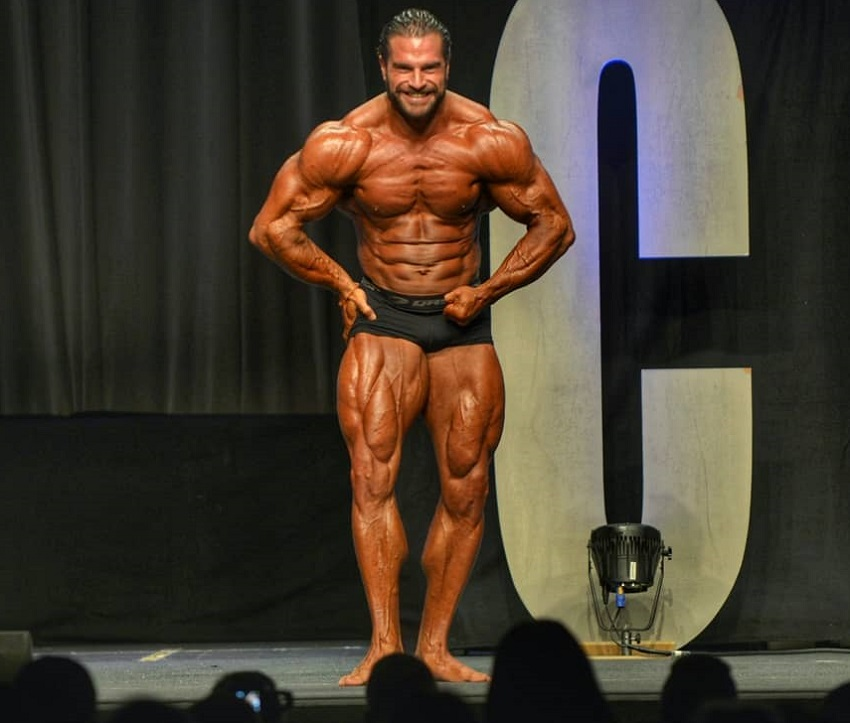 David Hoffmann posing on the bodybuilding stage showing off his swole and ripped muscles