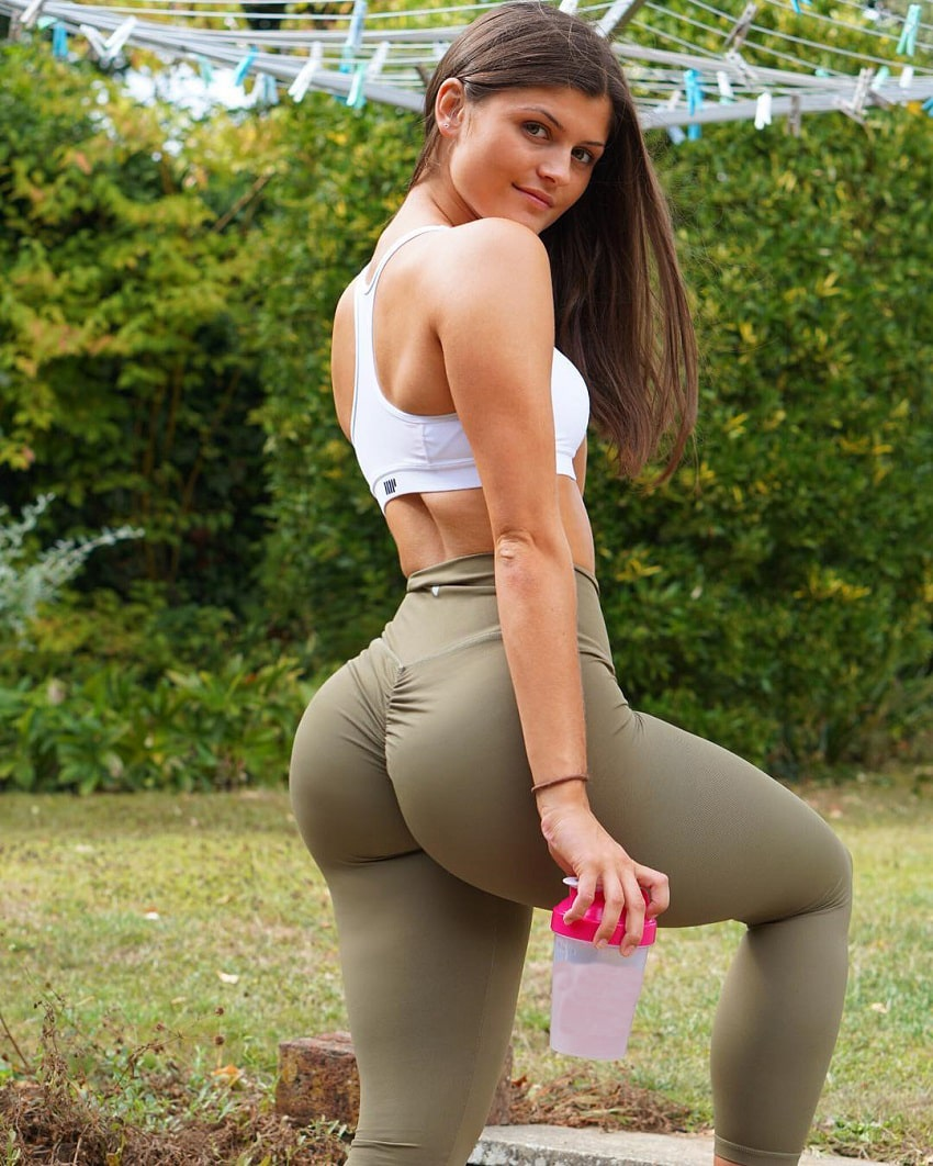 Elle Edwards posing with a shaker bottle looking curvy and fit