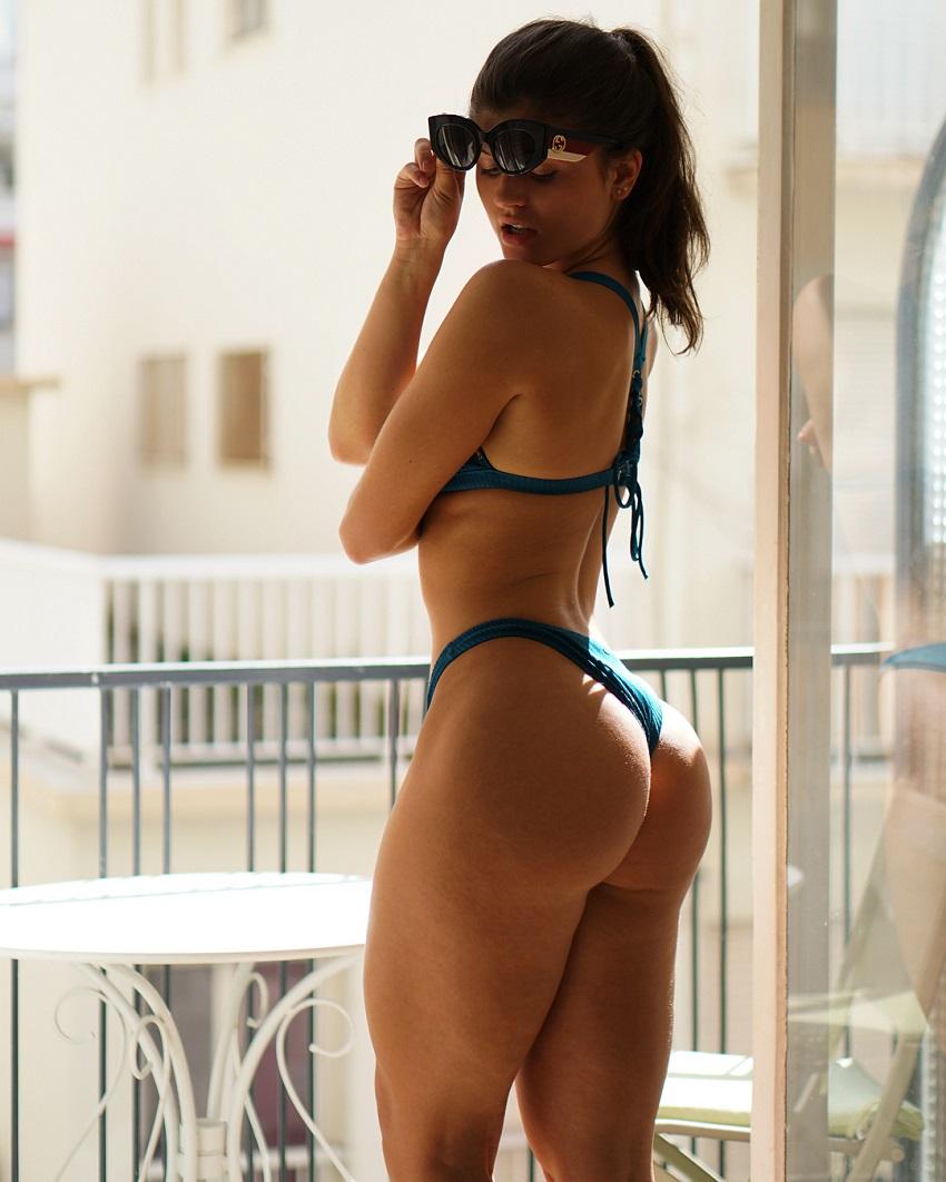 Elle Edwards showcasing her glutes in a bikini and sunglasses