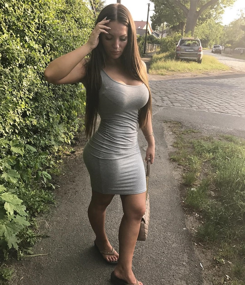 Gabriela Anova posing for the photo in a grey dress, looking curvy and fit