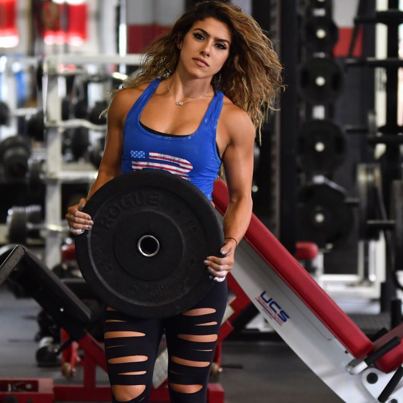 Heba Ali holding a weight plate as she poses for the camera, looking strong and aesthetic