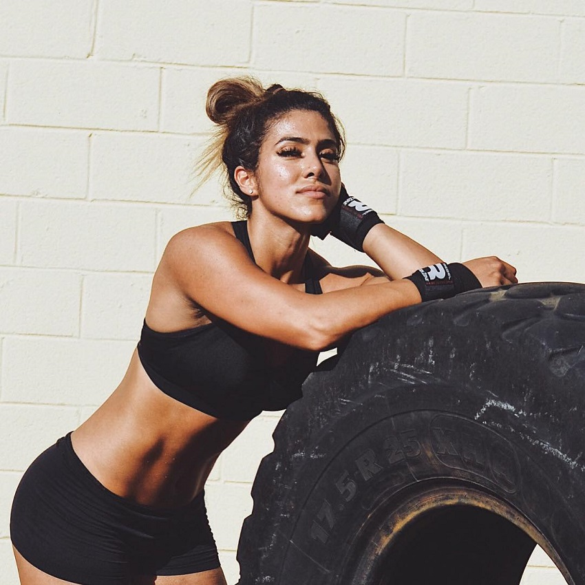 Heba Ali leaning against a tire looking strong and fit