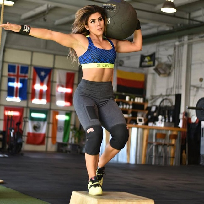 Heba Ali training with a medicine ball in a big warehouse