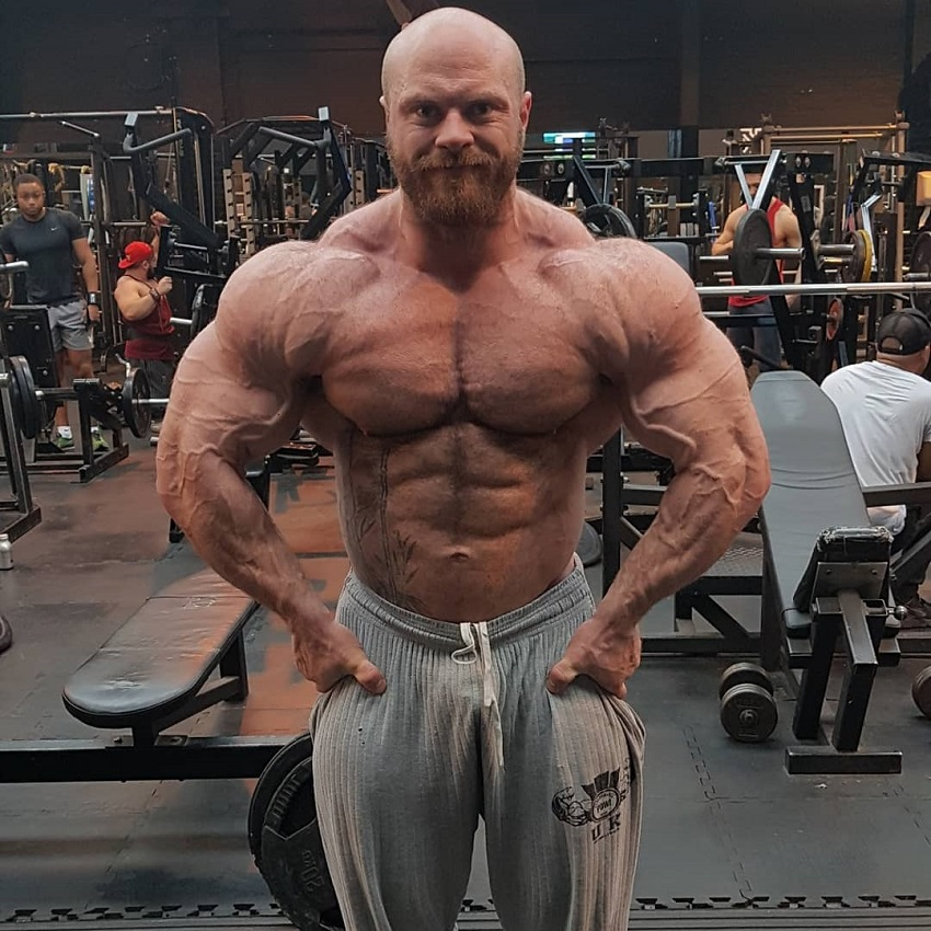 James Hollingshead flexing shirtless in a gym looking vascular, ripped, and huge
