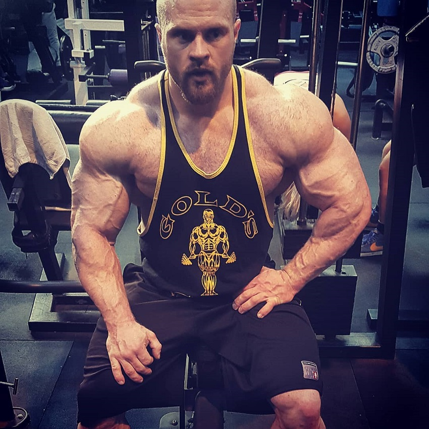 James Hollingshead sitting on a bench in the gym looking huge and ripped